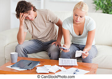 Stressed couple calculating their expenses in the living...