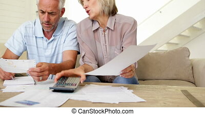 Stressed couple working out their bills on the couch at home...