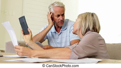 Stressed couple working out their finances - Stressed couple...