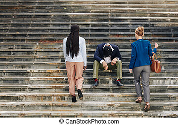 Stressed coworker sitting on steps