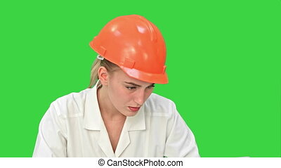 Stressed female engineer in helmet checking constraction plan on a Green Screen, Chroma Key.