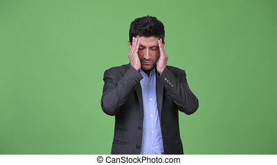 Stressed Hispanic businessman having headache - Studio shot...