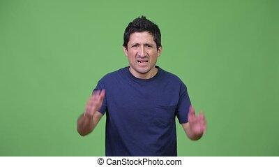 Stressed Hispanic man not wanting to hear something - Studio...