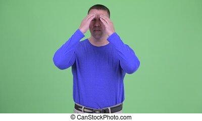 Stressed macho mature man getting bad news - Studio shot of...