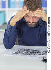 stressed male architect under pressure in office