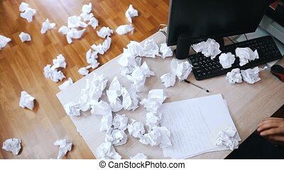 Stressed man crosses out what is written and throws crumpled...