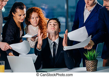 stressed male worker raises his hands and says please God while his colleagues ask him to do the job