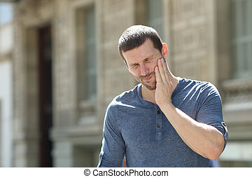 Stressed man suffering tooth ache in the street