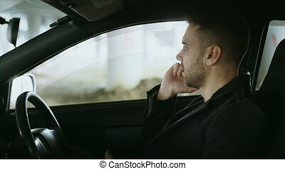 Stressed man swearing and talking phone while sitting inside car outdoors