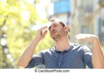 Stressed man sweating suffering heat stroke a warm day