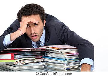 Stressed man under lots of pressure at work