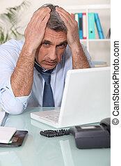 Stressed man using laptop