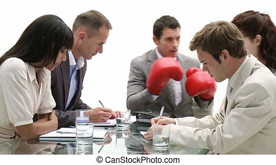 Stressed manager wearing boxing gloves in a meeting
