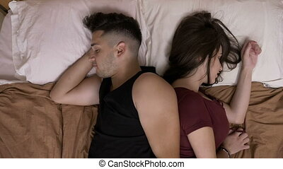Stressed married couple laying in bed back to back trying to...