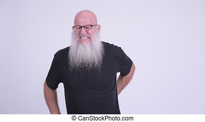 Stressed mature bald bearded man having back pain - Studio...