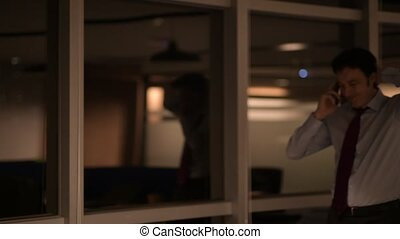 Stressed Mature Businessman In Office At Night Talking On Mobile Phone