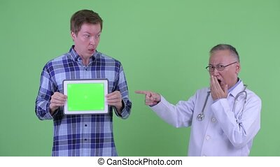 Stressed mature Japanese man doctor with young man showing digital tablet and looking shocked