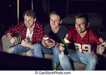 Stressed men watching match in concentration