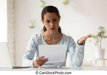Stressed millennial mixed race woman reading paper with bad news.