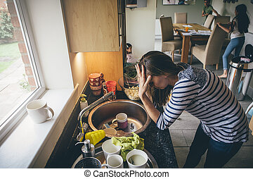 Stressed mum at home. She has her head in her hands at a messy kitchen sink and her children are running round in the background.