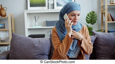 Stressed Muslim woman in hijab talking on mobile phone with...
