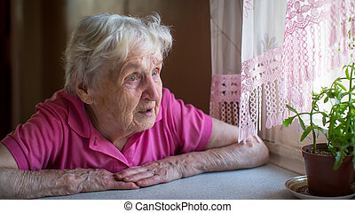 Stressed older woman sitting at the table.