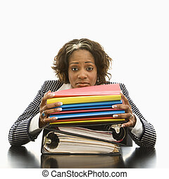 Businesswoman resting head on large stack of books and files looking overwhelmed.
