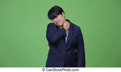 Stressed overweight Asian businesswoman having neck pain
