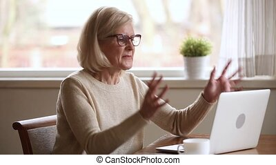 Stressed senior businesswoman annoyed with stuck laptop or...