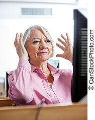 Stressed Senior Woman Looking At Computer In Classroom