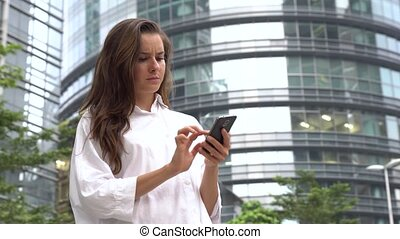 Stressed serious businesswoman work on smartphone.
