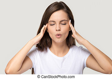 Stressed teen girl calming down massaging temples isolated on background