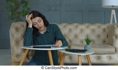 Stressed woman calculating bills and expenses at home