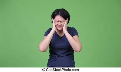Stressed woman covering ears from loud noise - Studio shot...