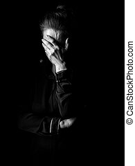 stressed woman in dark dress isolated on black background