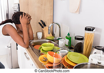 Stressed Woman Leaning Near Kitchen Sink Looking At Utensils