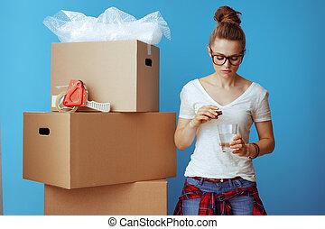 stressed woman near cardboard box drinking sedative on blue...