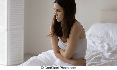 Distressed young woman touch belly stomach suffer from miscarriage or abortion, unhappy sad millennial female have stomachache, struggle with eating disorder or bulimia, health problem concept