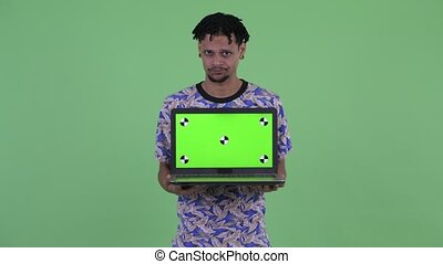 Stressed young African man showing laptop - Studio shot of ...