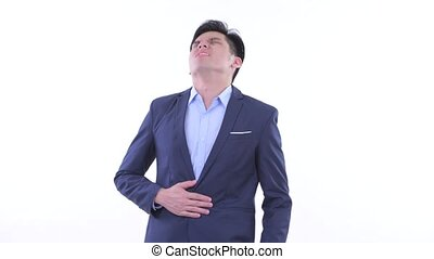 Studio shot of young handsome Asian businessman wearing suit isolated against white background