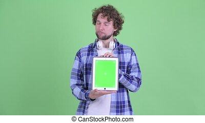 Stressed young bearded hipster man showing digital tablet and getting bad news
