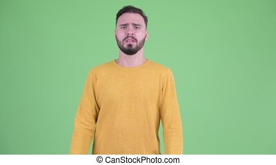 Stressed young bearded man getting bad news - Studio shot of...