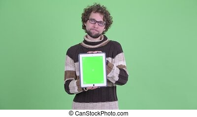 Stressed young bearded man showing digital tablet and getting bad news