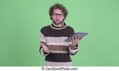 Stressed young bearded man using digital tablet and getting bad news