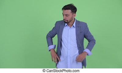 Stressed young bearded Persian businessman thinking and...