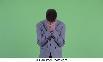 Stressed young businessman getting bad news - Studio shot of...