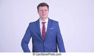 Studio shot of young handsome businessman wearing suit against white background