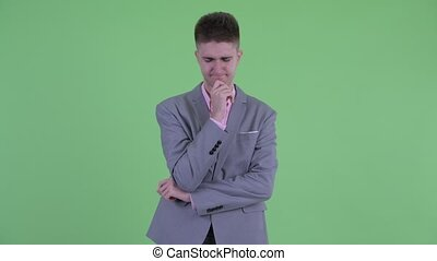 Stressed young businessman thinking and looking down -...