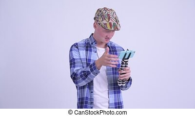 Stressed young hipster man as vlogger fixing phone on tripod...