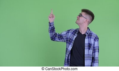 Stressed young hipster man pointing up and looking upset